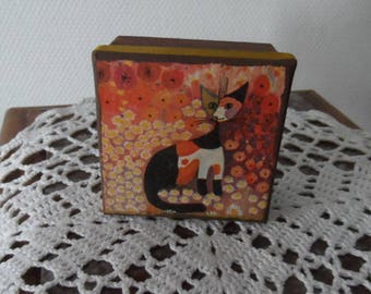 Square cardboard box decorated with paint and and top with a funny cat