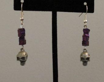 Skull earrings adorned with purple flat beads