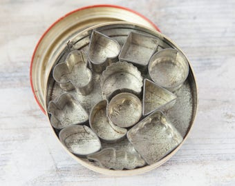 Vintage Rustic Tin Canape Cutters, and round tin container (set of 12). See item details for full description.