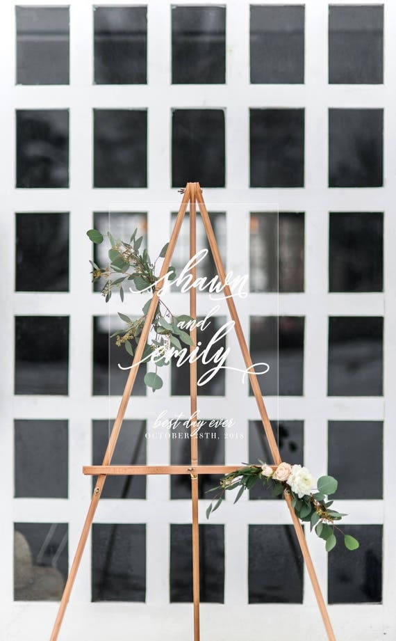 acrylic wedding sign with greenery at a modern wedding