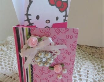 "Hello Kitty mini album (paper) w/ pockets, 3"" x 4 -1/2"" w/ matching gift bag, HK tags, gold bow, pink, white, green, 8 pockets, 26 tags."