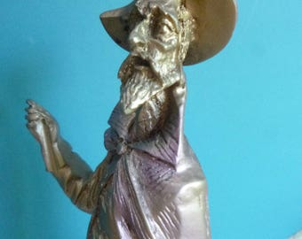 Metal Don Quixote standing on wooden pedestal.