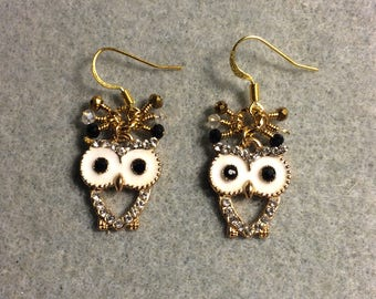 White, gold and black enamel and rhinestone owl charm earrings adorned with dangling black, gold and clear Chinese crystal beads.