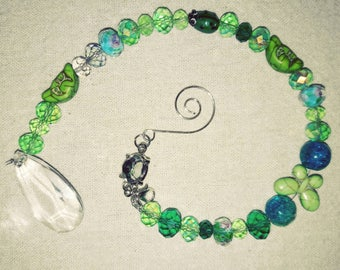 Green crystal beaded suncatcher with hook attached and comes with window suction cup.