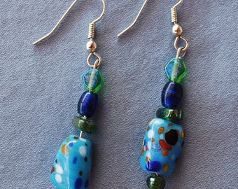 Beautiful earrings made with blue beads, painted with red, blue, orange, white and black, blue and green beads, silver fish hook wires.