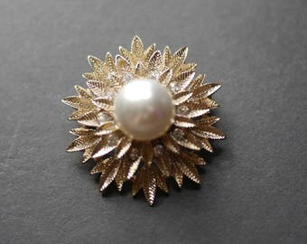Starburst brooch, gold tone with large central faux pearl and rhinestones on leaf pattern base