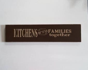 "Sign: ""Kitchens bring families together"" painted wood."