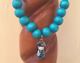 Little girls turquoise cheesewood beaded stretch necklace with adorable Geisha Kokeshi doll charm