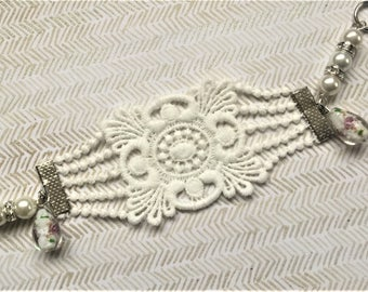 Bracelet with applique in very pretty and delicate white lace on claws in silver metal.