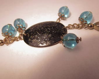 Bracelet gold chain and a glittery black medallion and blue beads