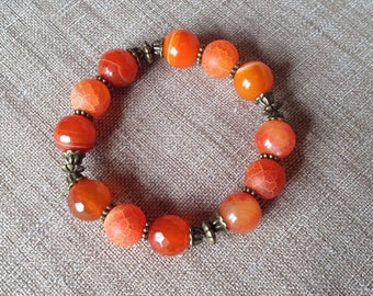Stretch bracelet different orange agate and bronze beads.
