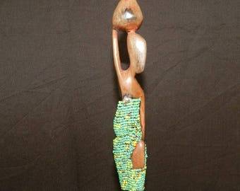 Skinny woman statue in yellow and green beads and ebony from Africa. Height 36 cm