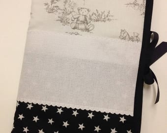 Health book has embroidery stitch crosses, stars and grey black bear.