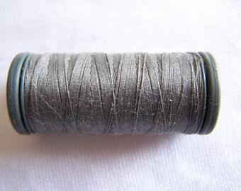 Spool of fils à coudre DMC, smoke gray, special machine (4037)