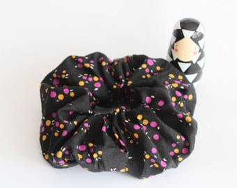 Black fabric elastic scrunchie with orange pink polka dots