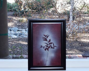Silhouette of pressed plant burgundy background stain