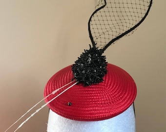 A red fascinator mini hat with black veil and studs