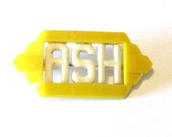 Yellow plastic deco pin with initials