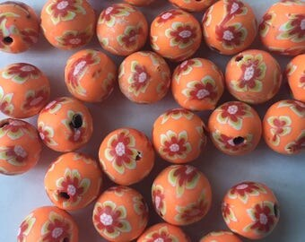 Pack of 14 x 10mm polymer clay round orange with red coloured flower beads.