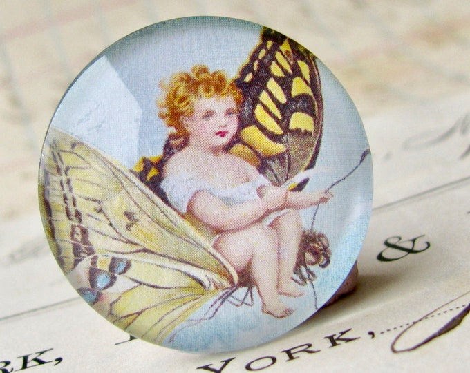Child riding a butterfly, handmade 25mm round glass cabochon, fantasy stories, bottle cap, 1 inch, from our Winged Wonders collection