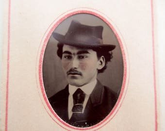 antique tintype with paper frame - young man with mustache and hat, rosy cheeks