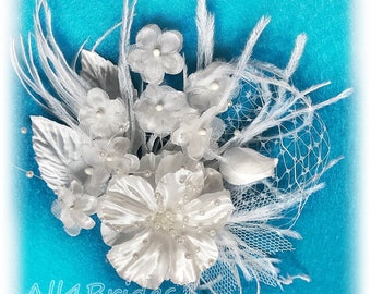 White bridal hair clip, pearls, french netting, ostrich feathers and silk flowers.  Wedding bridal hair clip