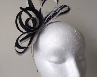Black and white loop fascinator with feathers and netting on a silver headband.