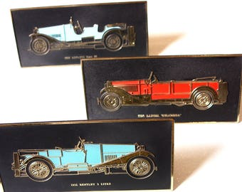 Three classic vintage car plaques, with stands.
