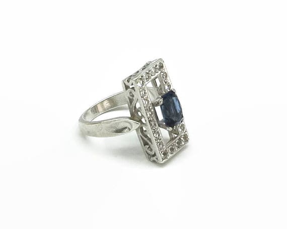 Sterling silver ring with central blue stone and multiple cubic zirconia stones on rectangular plate with filigree sides, size N.5 / 7