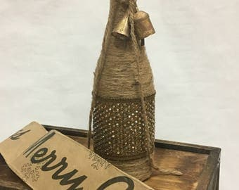 Twine-wrapped wine bottle with gold ribbon and rustic bell accent.