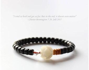 Bracelet noir avec une rose blanche comme une pierre de noix de coco