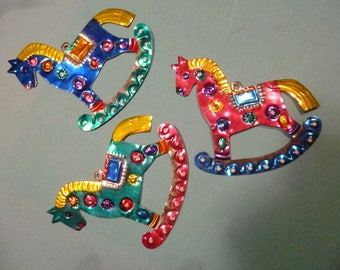 Three tin rocking horse Christmas ornaments made in Mexico