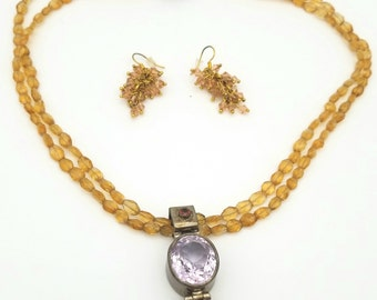 Double strand citrine, pendant has an amethist and citrine stones. Magnetic clasp and matching earrings.
