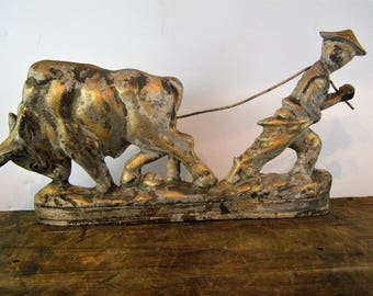 Vintage Cast Iron Door Stop. Intricate Casting Detail. Asian Plowman with Ox. Beautifully aged and distressed Patina. Chippy Gold Paint.