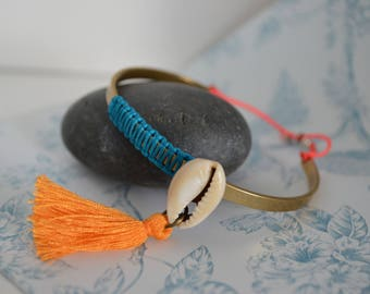 Brass braided bangle with a seashell and pompon