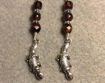 Silver duck-billed platypus charm dangle earrings adorned with brown Czech glass beads.