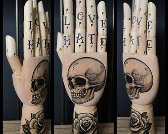 Wooden hand mannequin with original drawings of a skull and rose