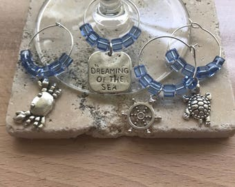 """Beach Decor. Set of 4 and 8 Wine Charms """"Dreaming of The Sea"""" with Dreaming, Turtle, Crab and Ship' Wheel charms. Handmade in the UK."""