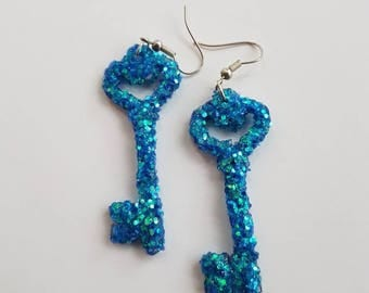 Sparkly blue key earrings made from wood and covered in glitter.