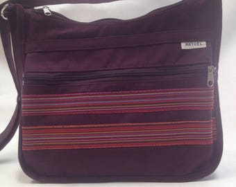 a purple shoulder bag decorated with stitched fancy stripe fabric
