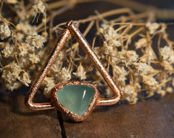 Triangular copper pendant with green-blue stone.