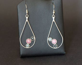A handmade pair of drop earrings, each with a set of three kiln fired enamels