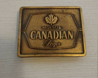 Vintage 1977 Molson Canadian lager belt buckle and bottle opener made in the USA brass 3in x 2.5in