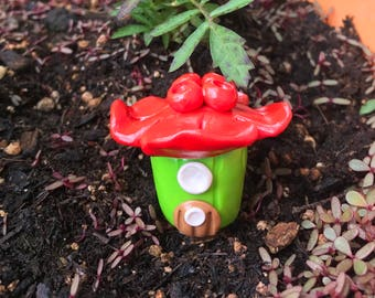 Bright green gnome home/fairy house with red flower roof