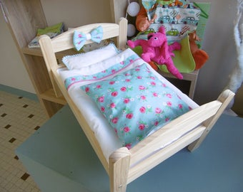 Small wooden doll bed and bed linens