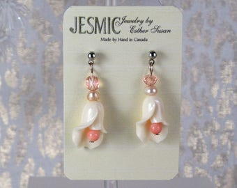 "Feminine. Delicate. Cream Lillies with Coral Centers.  Classic Pearl and Crystal mini-Accents. Silver Finish Posts. 1.5"" Long"