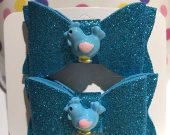 Beautiful foam bow with custom appliqué (glittery blue with blue chicken cabochon) on an alligator clip. (Set of 2).