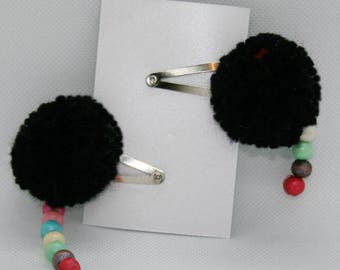 A pair of handmade small black pom pom girl hair clips, red spot, multicoloured hanging beads