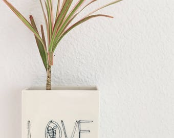 medium porcelain planter / wall vase screenprinted text LOVE blue.