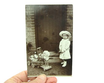 Antique Photo Postcard. Little Girl Playing w/ Hobby Horse Toy & Wagon. Edwardian Fashion. Real Photo RPP Photograph. 1910s Collectible